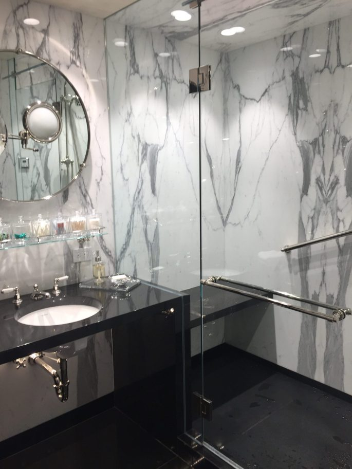 Master bathroom shower in calacatta marble slab walls with black granite floor, sink and bench
