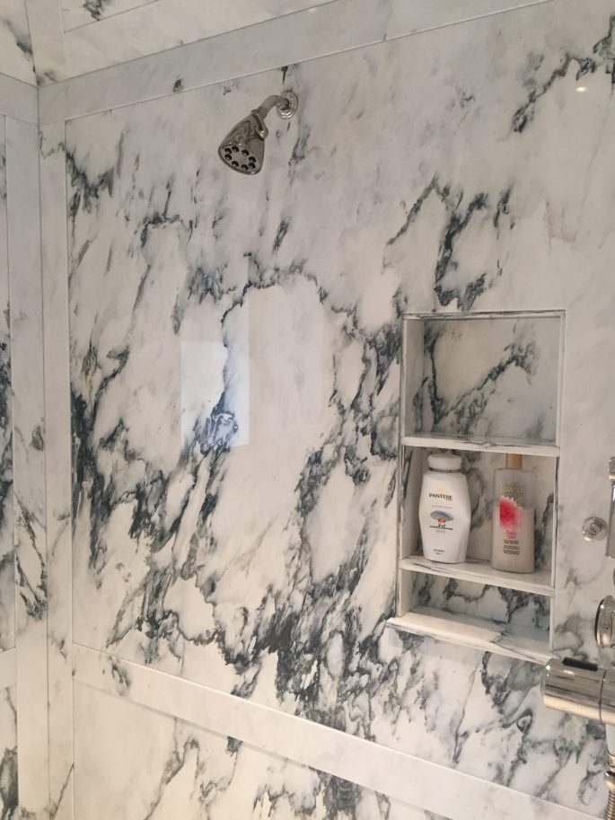 Paneled shower walls in paonazzo white marble