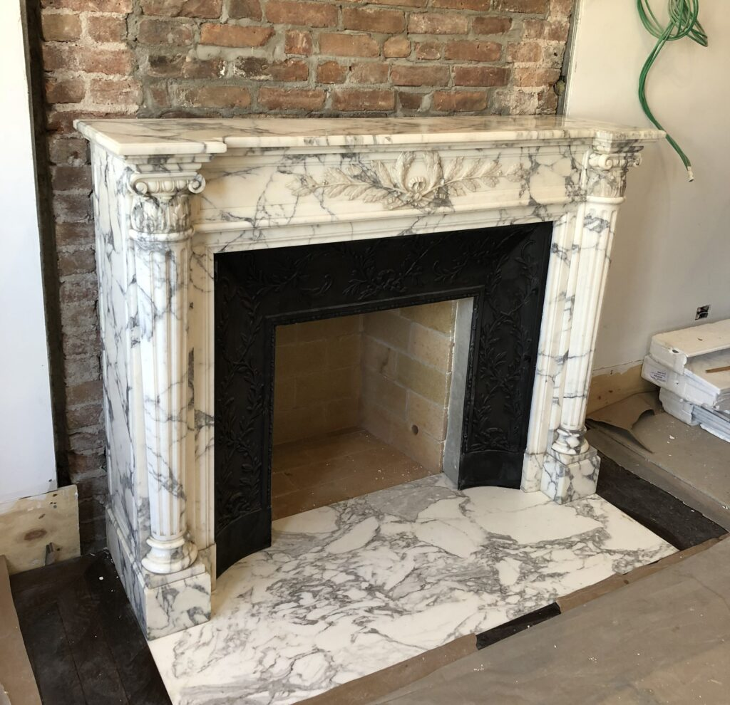 Antique white marble mantel installed