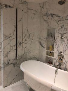 Master bathroom in calacatta marble slab and thassos tile floor