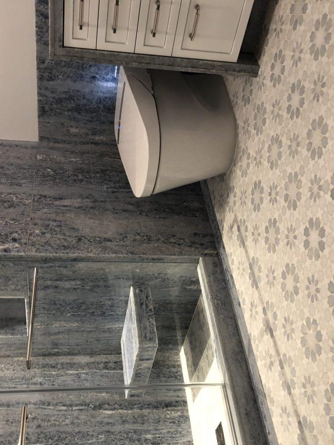 Bathroom in blue quartz slab with custom mosaic floor