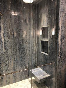 Bathroom shower in blue quartz slab with custom mosaic floor