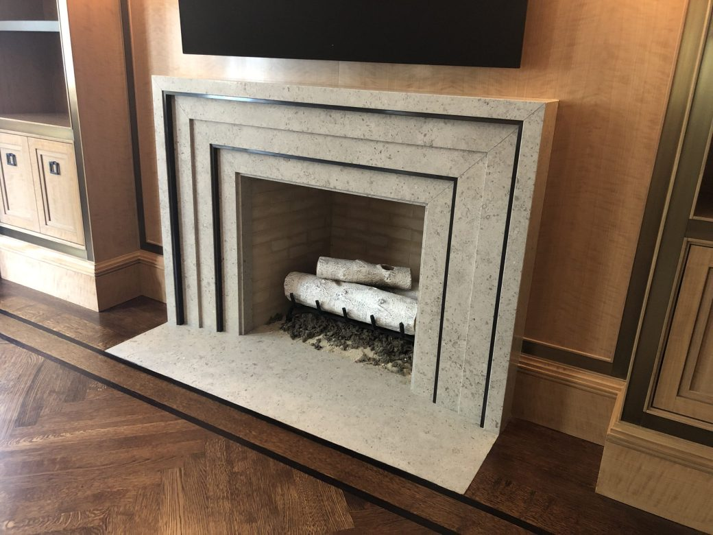 Library custom limestone and bronze fireplace mantel