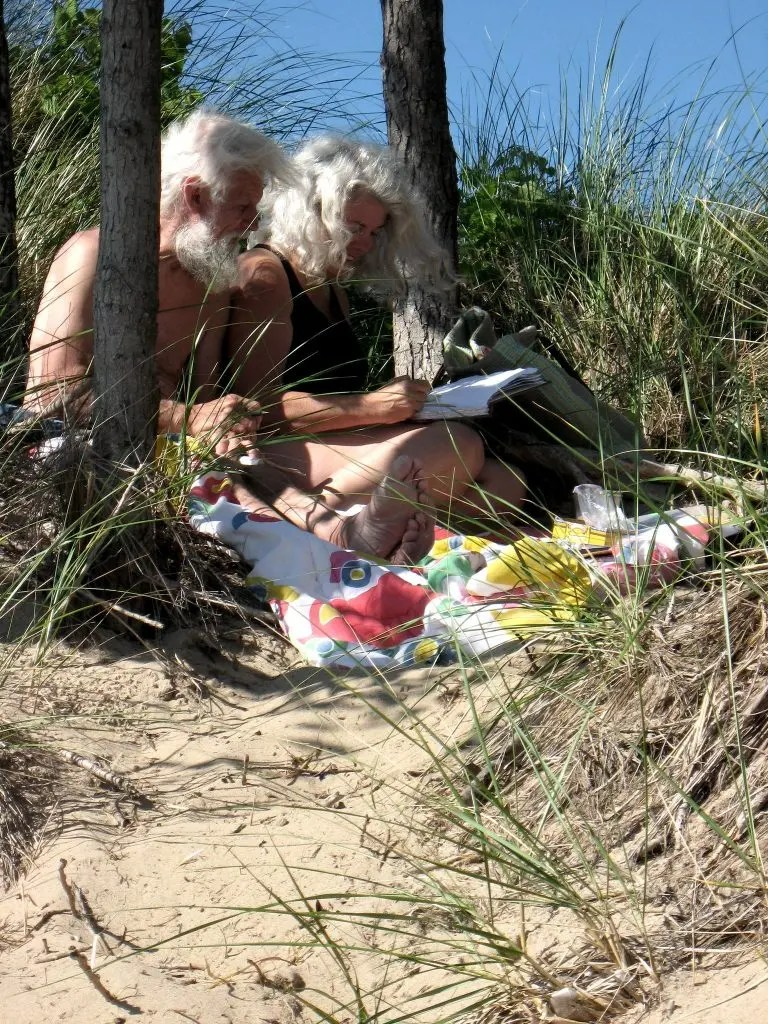 A photo of two white haired people drawing and writing while nestled in a dune