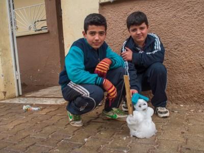 Turkish boys pose with their snowman, David Gross