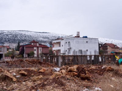 Snow in the Syrian hills above home construction in the Turkish town of Reyhanli, David Gross