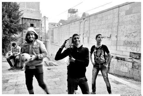 Adolescents playing football in Cairo and posing