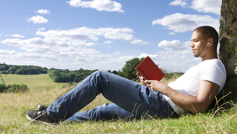 Close up of a man reading a book under the shade of a tree