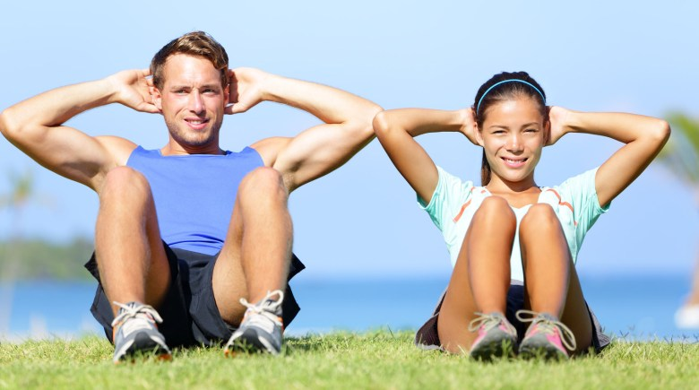 Sit ups - fitness couple exercising sit up outside