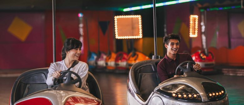 Two young friends riding bumper cars at amusement park