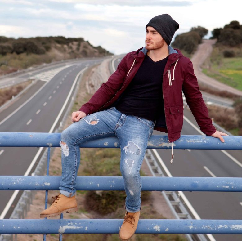 Handsome man at the top of a bridge over a highway