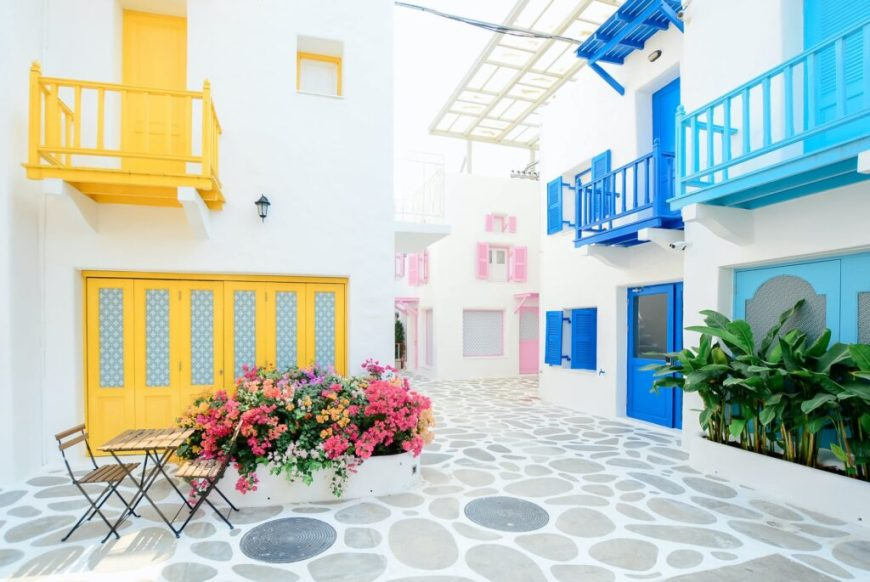 architectural photography of three pink blue and yellow buildings