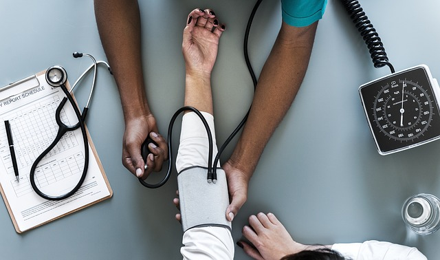aerial photo of doctors arms taking the blood pressure of a patient