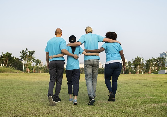 4 people, 2 women, 2 men, wearing light blue t-shirts with their arms round each other. They are stood in a line with their backs to the camera
