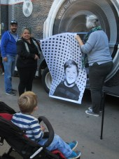 Child viewing freshly minted portrait from Inside Out Project truck