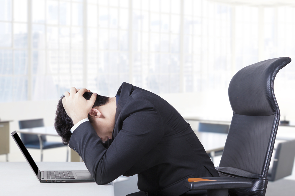 Man hunched over his desk at work