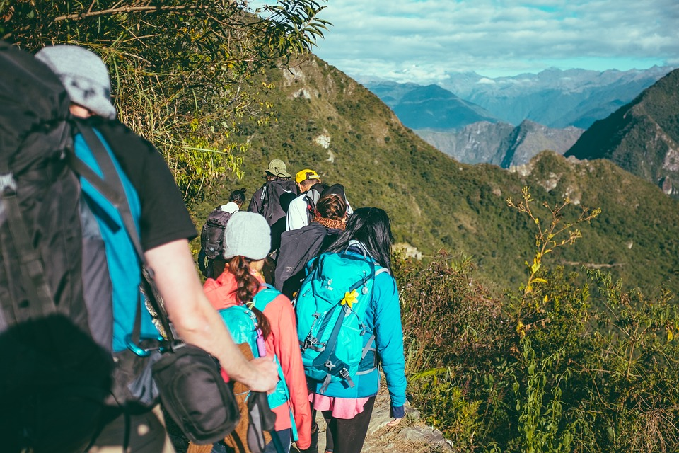 Team of hikers following leader down a mountain trail