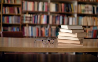 image of library books on table with pair of eyeglasses next to them