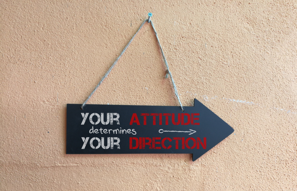 """Sign in the shape of an arrow with the words: """"Your attitude determines your direction"""""""