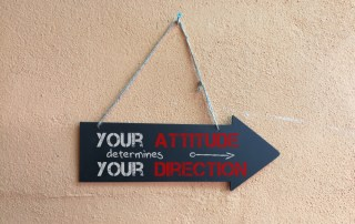"Sign in the shape of an arrow with the words: ""Your attitude determines your direction"""