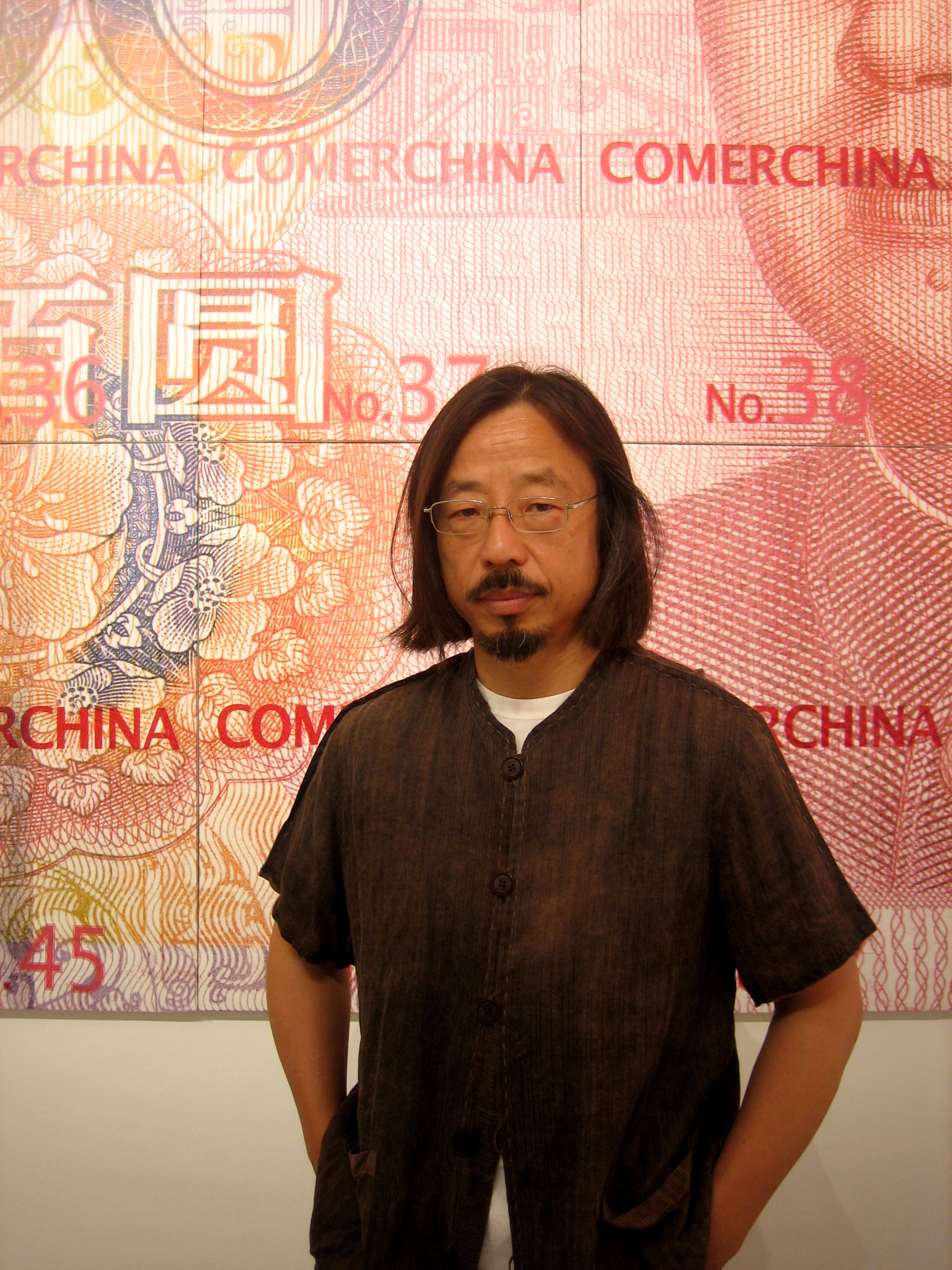 Artist Huang Rui standing in front of the Comerchina exhibition.