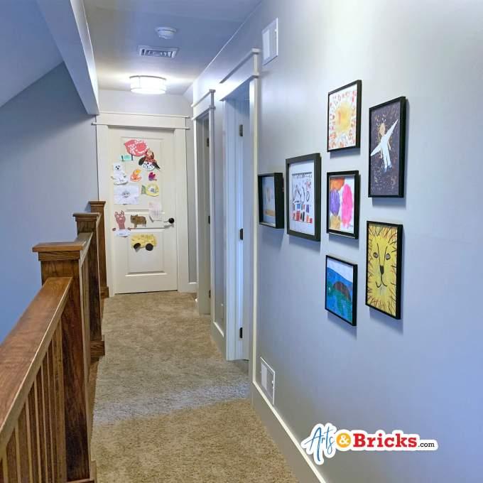 Hallway featuring kid artwork - kid artwork gallery wall.