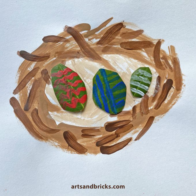 Kid painted bird's nest with painted leaf art Easter Eggs