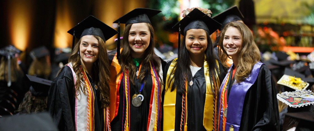 A group of four female graduates pose. Spring commencement at the University of Tennessee, Knoxville (College of Arts and Sciences ceremony). Photo by Steven Bridges