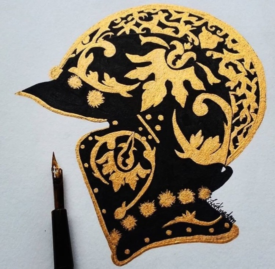 a knight's helmet in black and gold