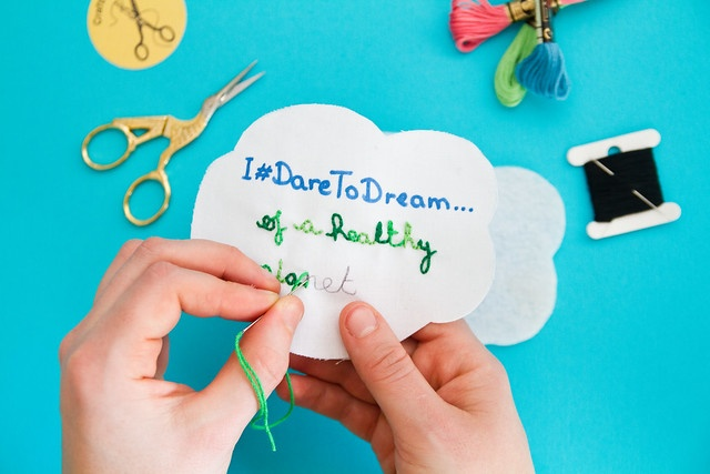 hands stitching I dare to dream of a healthy planet on cloud-shaped material