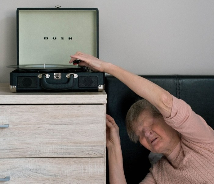 a woman is next to a record player and reaching up to touch it