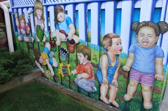 Little kids on fence at Child Network Services