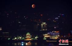 """10月8日晚,""""红月亮""""亮相江南名楼滕王阁上空。(多重曝光图片)中新社发 刘占昆 摄"""