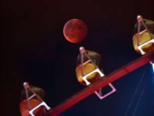 A total lunar eclipse is seen behind a ferris wheel in Tokyo on Oct. 8, 2014.