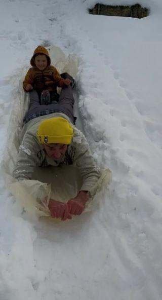 Hem karla kaplı evinin yolunu açtı, hem de torununu eğlendirdi