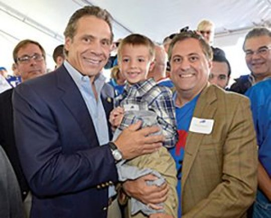 Andrew Cuomo holds Steve Pigeon's nephew Landon at an event with Pigeon.