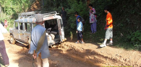 Jeep gets stuck in muddy road after heavy rain falls.  The driver and volunteers get us out within 20 min.