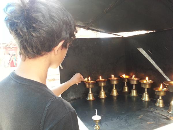 Son lighting candles/diya's, offering prayers July 2015, Kathmandu, Nepal