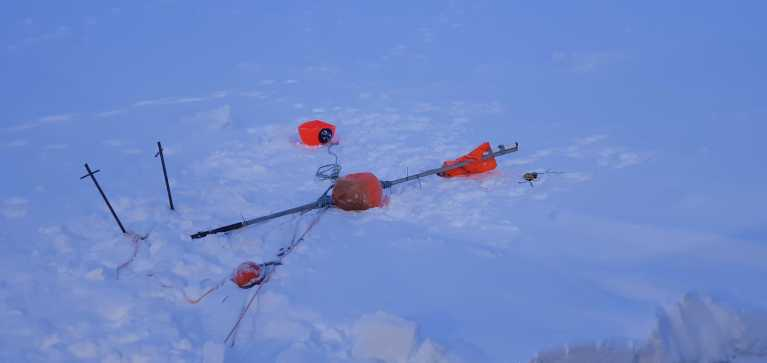 Leftovers from the polar bear visit: The flagpole destroyed, the metal poles (on the left) bent, the AIS on the ice. Photo: Silje S. Wollberg (IMR).