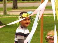 waldorf early childhood student wearing may day crown and smiling walking around may pole
