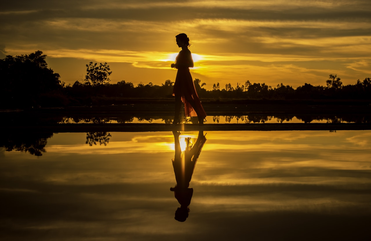 Silhouette of a woman standing on a dock, with a sunset in the background, reflection in clear water. Trees surrounding.