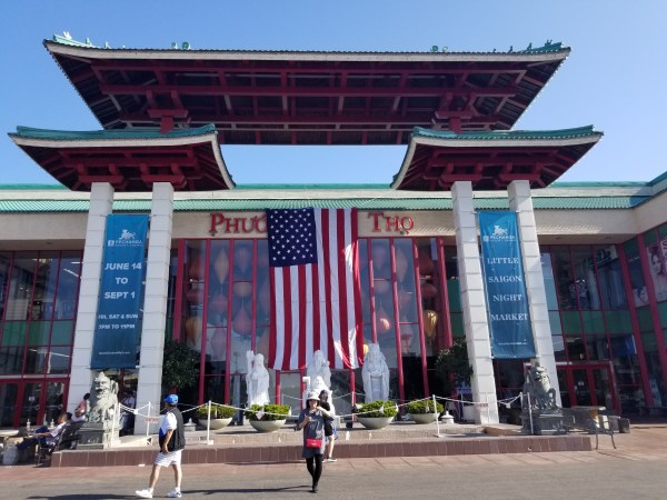 Image description: Asian Garden Mall in Westminster, California. People are walking about in the afternoon. An American flag spills down from the top.