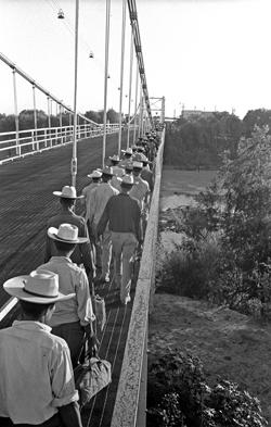 Long line of men crossing a bridge.