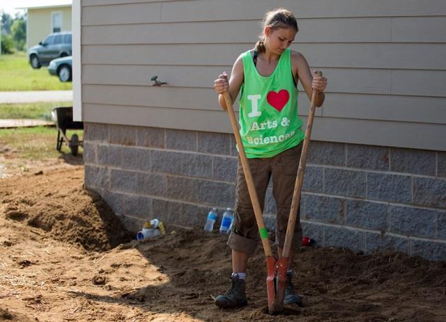 Woman using a post-hole digger