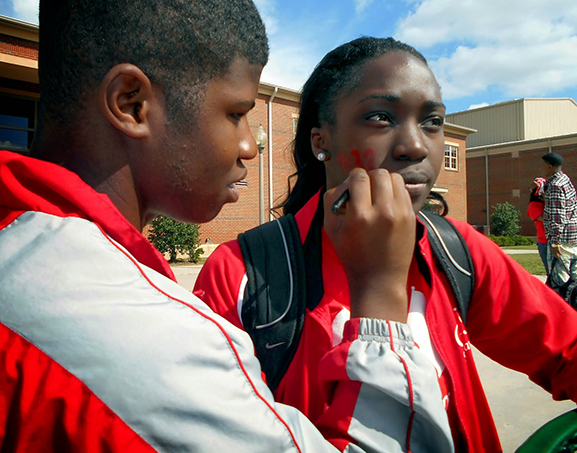 a high school student applying paint to another student's face
