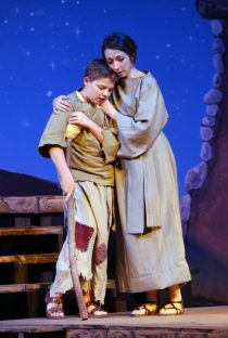 A young boy and his mother perform on stage