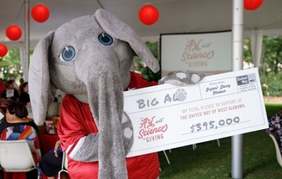 Big Al holds a big cardboard check for $395,000 for the United Way campaign