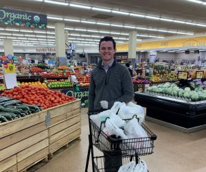 Michael Arundel with a cart of bagged groceries in the grocery store.