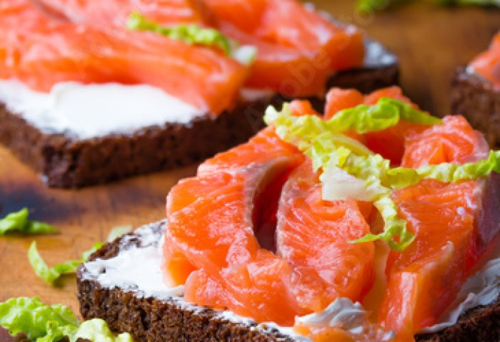 Sandwich With Cereals Black Bread And Salmon On Wooden Board
