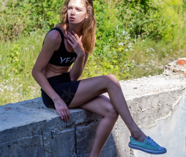 Young Charming Sexy Teen Girl With Long Hair In A Short Mini Skirt And Tank Top
